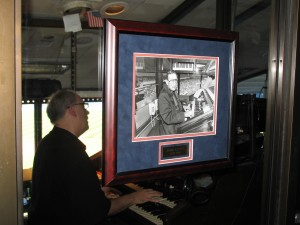 Ed Alstrom playing the organ on the final day of Yankee Stadium behind a framed picture of Eddie Layton